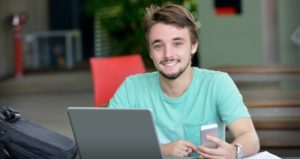 male college student with phone and laptop
