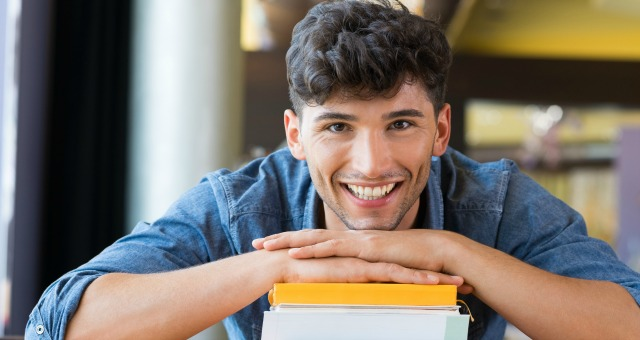 male college student with stack of books