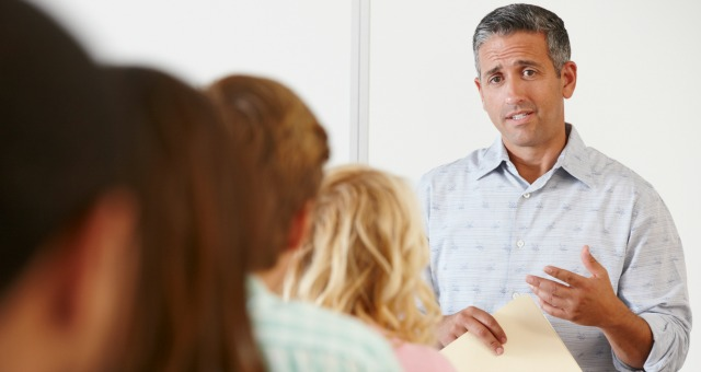 Male professor talking with students