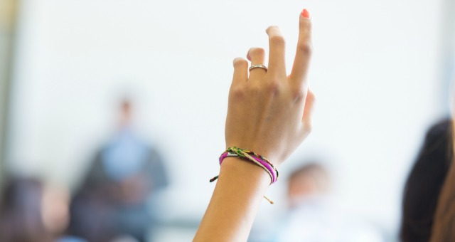 student raising hand on class