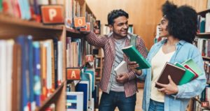 Two diverse students select cultural content from library