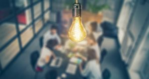 Students collaborate in group with light bulb idea above them