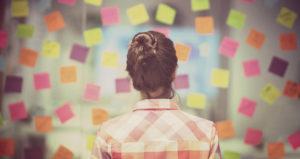Woman overlooks sticky notes and lessons from the week