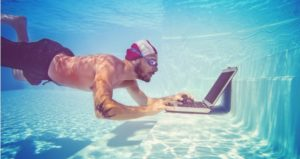 Man swimming underwater also checks his email on his laptop in the pool