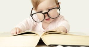 Baby with glasses looks at huge book