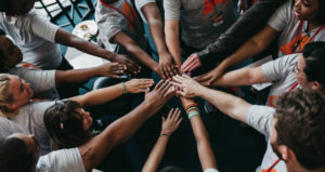 A circle of diverse hands joins together