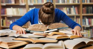 Student surrounded by books and feeling overwhelmed