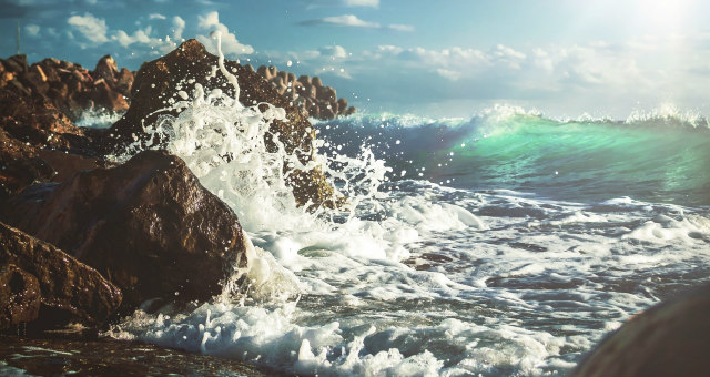 Tide crashes against rock in metaphor representing online students who are struggling