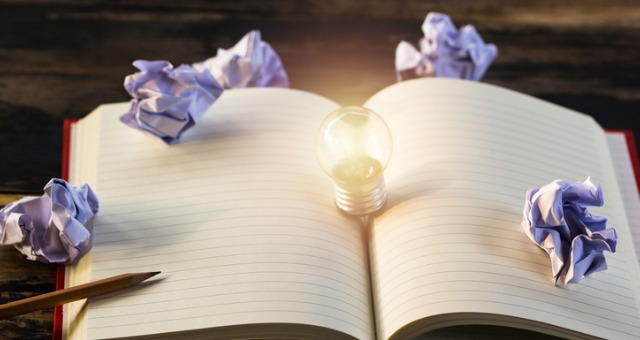 Blank notebook with idea lightbulb emerging from it