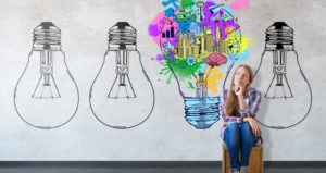 Girl sits with light bulbs, including one full of ideas for redesigning an online class