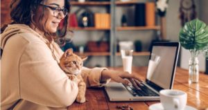 Student engages in online class with cat in lap