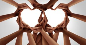 Hands emerge together to form hearts, symbolizing fairness and equality in the classroom