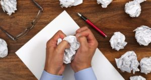 Student crumples paper while writing essay assignment
