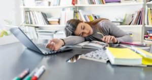 Student falls asleep at desk with computer, papers and books open