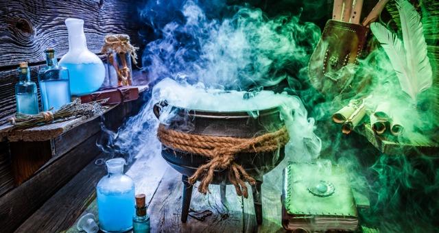 Black cauldron emits colorful smoke with potions and books surrounding it