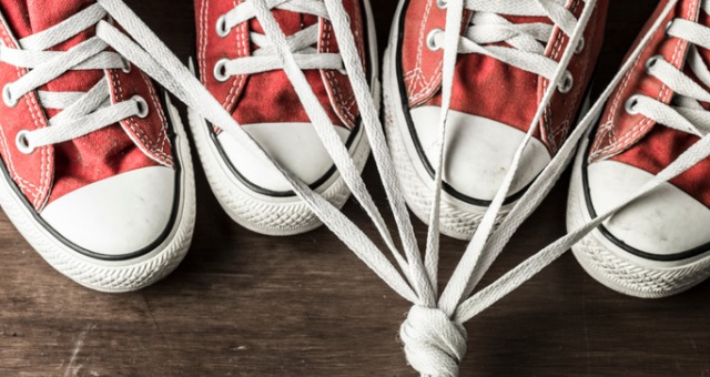 Four red sneakers tied together with shoe strings