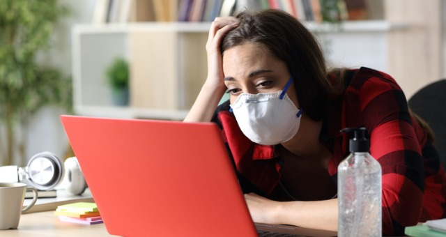 Student sits at computer with mask on looking defeated