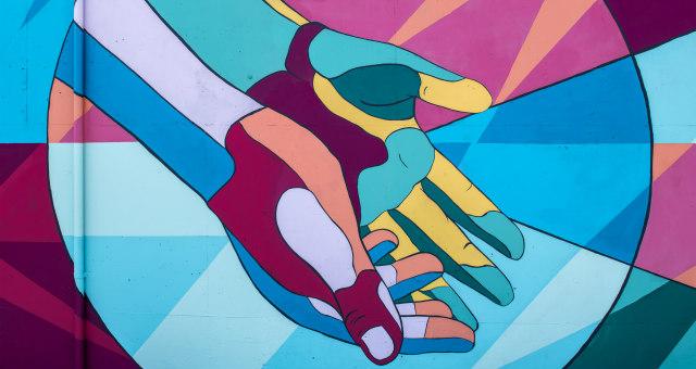 Multi-colored hands on graffiti wall