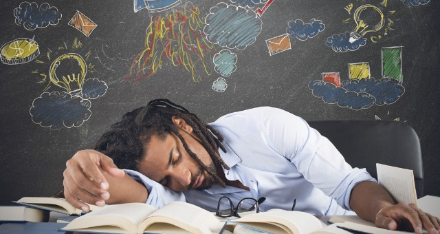 Teacher lays head on arm on desk with colorful chalkboard behind him