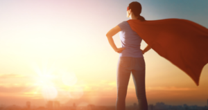 Woman in superhero cape stands facing sunset