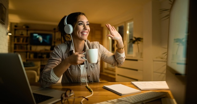 Student with headphones smiles and waves to computer screen while drinking coffee