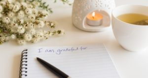 "notebook says ""I'm grateful for..."" with candle and tea in background"