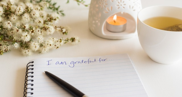 """notebook says """"I'm grateful for..."""" with candle and tea in background"""