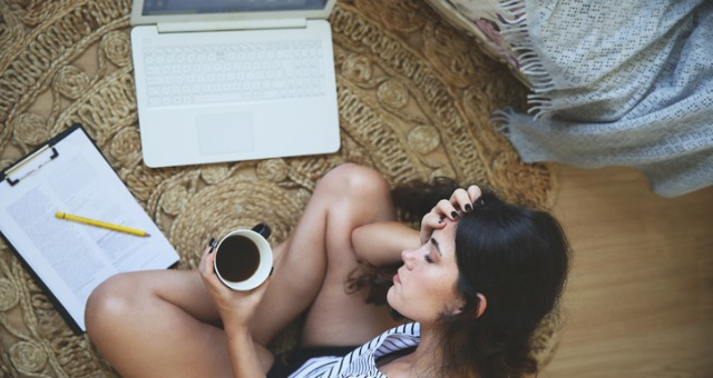 Looking down on girl sitting on floor as she holds coffee cup and puts head in hands in front of computer