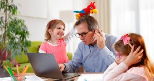 Father of two tries to work at computer while little girls place stuffed animals on his head and other one tries to do homework