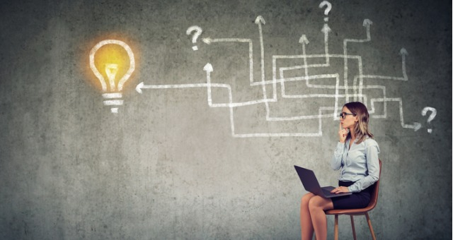Woman sits on chair with computer laptop with chalkboard behind her of arrows, question marks and a light bulb