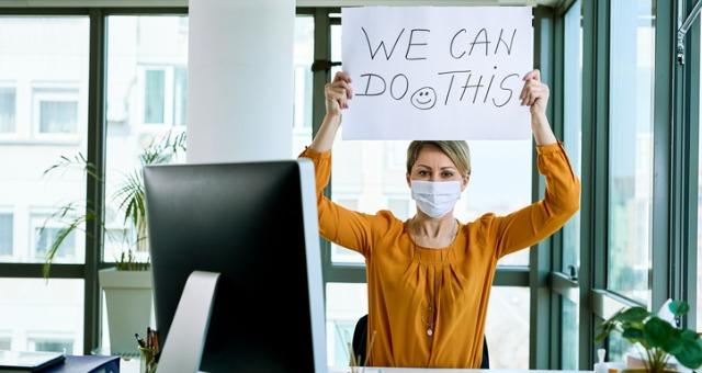 """Woman has mask on at computer desk while holding up sign that says, """"We can do this."""""""