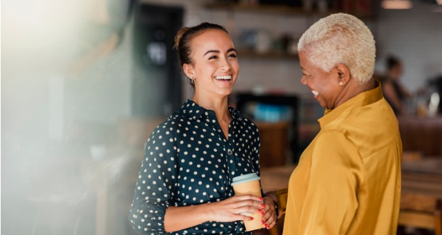 Two people laugh with one another while chatting and drinking coffee