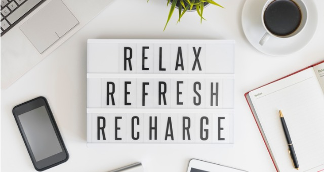 "Sign says ""Relax, refresh, recharge,"" with cup of coffee, phone, pen, paper and plant surrounding it"