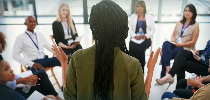 Person stands in front of others in educational training session