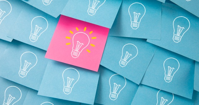 Sticky notes with light bulbs on them has one pink colored one that sticks out with light bulb lit up