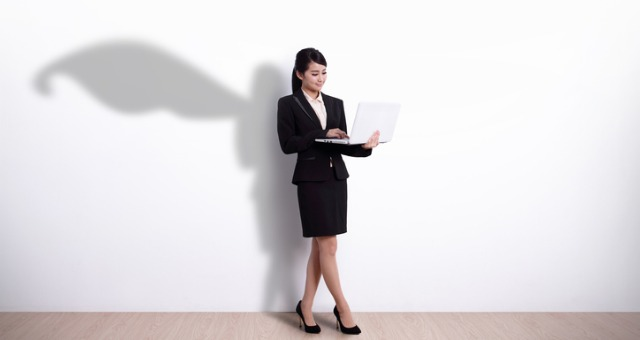 Woman holds computer with shadow of superhero cape behind her