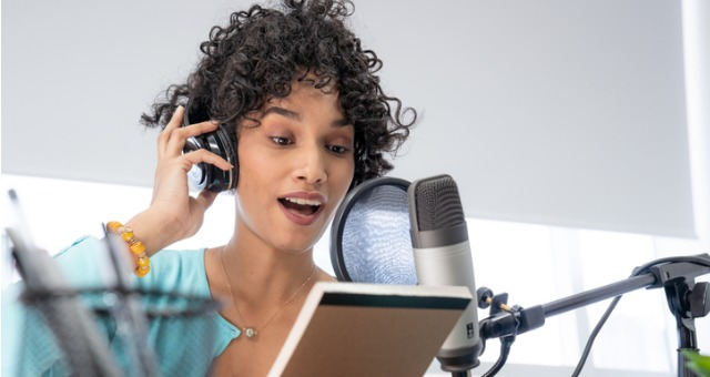 Student holds up notepad to ask questions over podcast microphone
