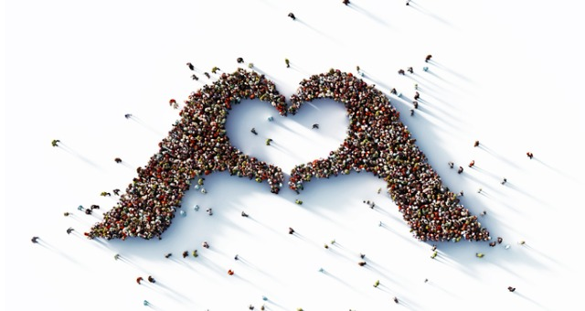 Crowd of people form hands in the shape of a heart