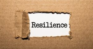 """Cardboard is pulled back revealing the word """"resilience"""""""