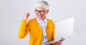 Woman holding computer and cheering for success