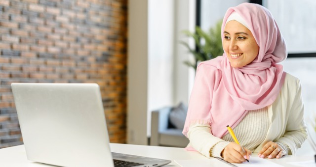 Young woman with hijab smiles at computer and writes something down at desk
