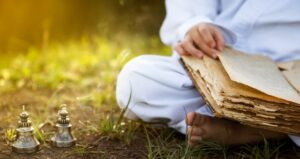 Person meditating and reading ancient script while reading on the ground