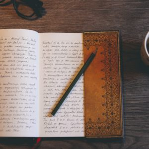 Book with writing and coffee mug and pencil laid open on the table