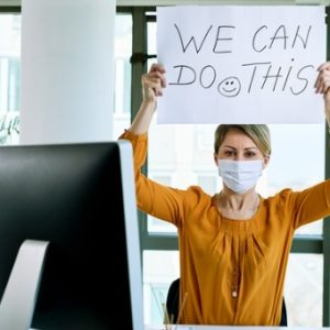 Woman has mask on at computer desk while holding up sign that says,