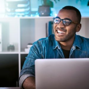 Man smiles while typing on computer