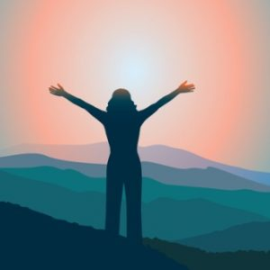 Person with hands in the air in success with sunset and mountains in background