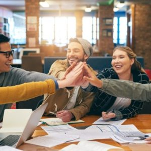Students sit at work table and give high five in middle