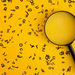 Magnifying glass with tiny letters surrounding it in the background