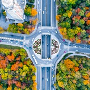 Roundabout features cars driving during fall and fall colored trees