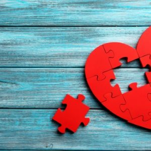 red-puzzle-heart-on-blue-wooden-background-picture-id520409842